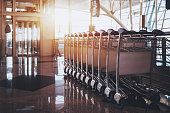 Close-up view row of multiple connected luggage carts stretching into distance parked in modern hall of airport terminal or railway depot station with elevator and glass facade in defocused background