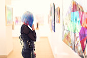 Young woman with beautiful dyed hair looking at fine art paintings. Paintings have the same colors as the hair. I replaced the original paintings with my photos.