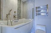 Contemporary bathroom design boasts a luxury Jacuzzi Walk-in Bathtub flanked by subway tiled interior accented with wide glass mosaic tiled vertical stripe