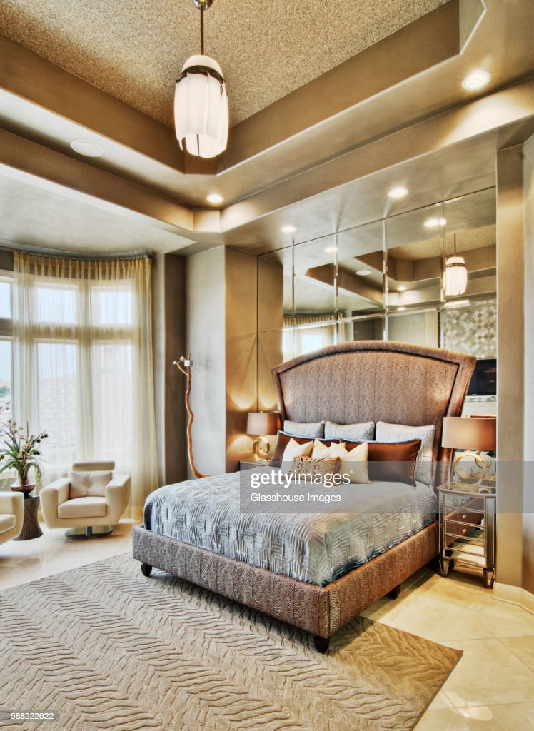 Contemporary Bedroom with a Double Bed with Upholstered Headboard and Mirrored Wall