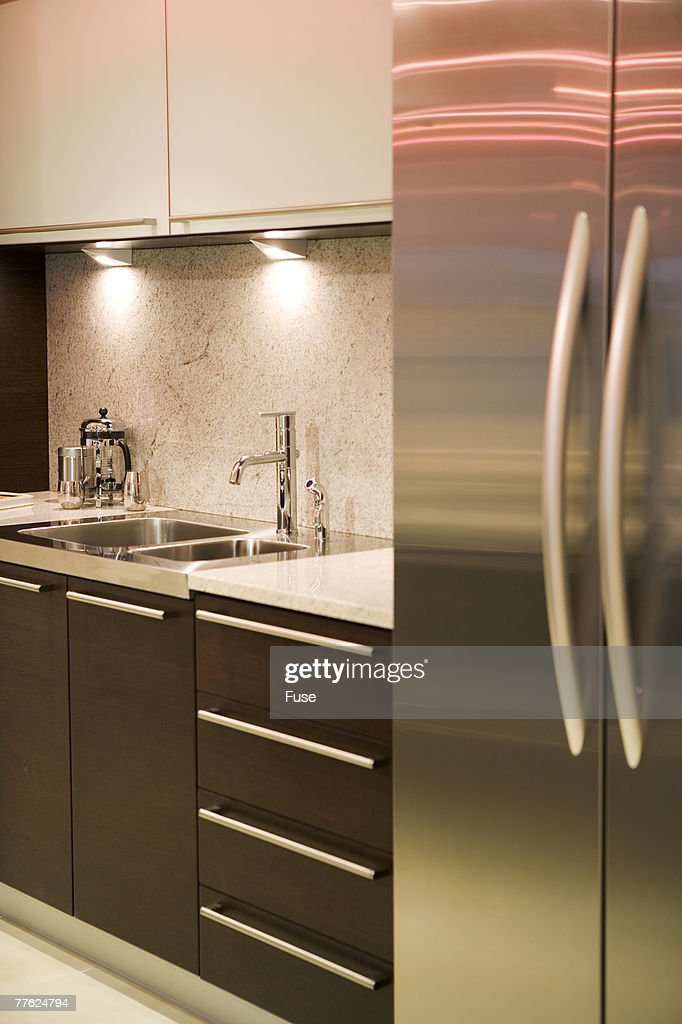A contemporary kitchen with stainless steel appliances and dark wood fittings stock photo - Modern kitchen with black appliances ...