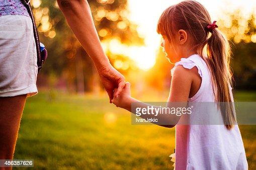現代的なウォーキングの母と娘公園の日没時