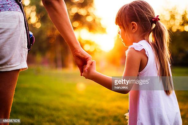 Contemporary mother and daughter walking in park at sunset