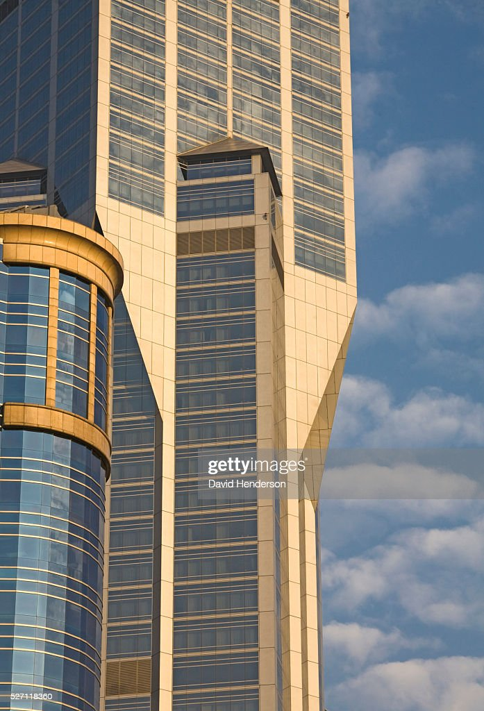 Contemporary skyscraper contrasted against blue sky and clouds : Stock Photo