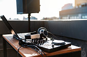 Modern music equipment with Dj mixer near laptop on table for party on roof. Large music column on background