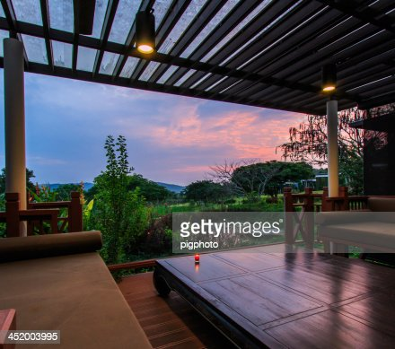 Contemporary terrace lounge with view of greenery at sunrise : Stock Photo
