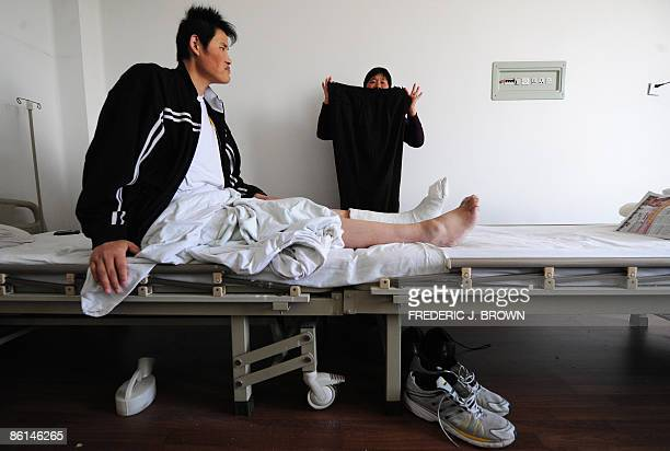 Contender for the world's tallest man 246 meter tall Zhao Liang recuperates from foot surgery as his mother displays how large his trousers are on...
