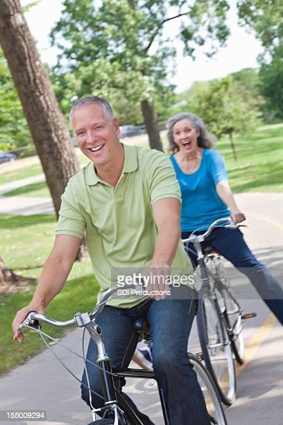 Inhalt und glückliche Paar auf einem Fahrrad im Park