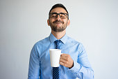 Closeup portrait of content handsome young man holding mug and enjoying drinking tea. Break concept. Isolated front view on grey background.