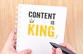 Content is King work on white ring binder notebook with hand holding pencil on wood table,Digital Business concept.