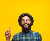 Cheerful bearded hipster in eyeglasses and hat pointing happily looking away on orange background.