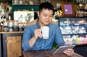 Content Asian man reading article and drinking coffee in cozy cafe. Pleased handsome young man relaxing in public place. Coffee house concept