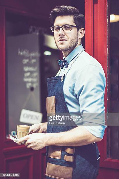 Content waiter is holding an espresso