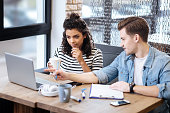 Discussing a project. Good-looking alert young woman and man sitting at the table and the girl looking at the laptop having a cup in her hand and the man pointing at something on the screen
