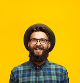 Portrait of young bearded hipster in hat and eyeglasses looking happily up on orange background.