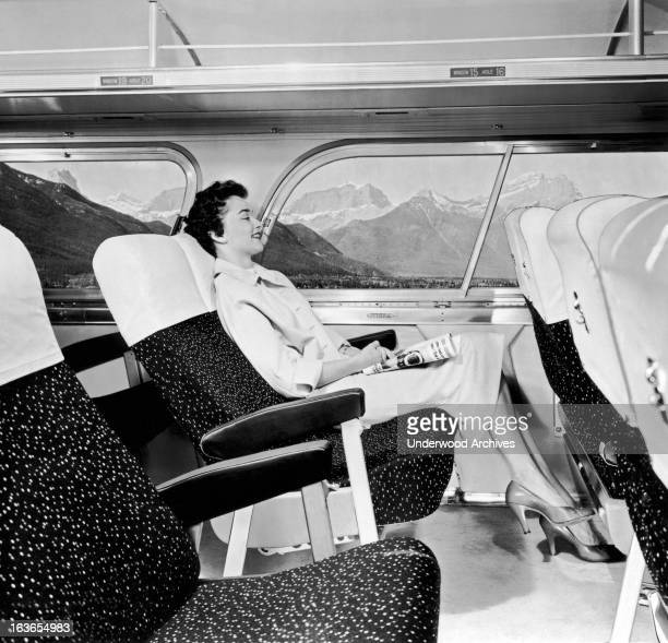 A contented woman passenger on a bus relaxes as they pass through the Rocky Mountains 1957