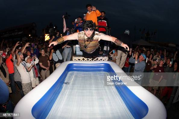 A contestant dives into a pool of water in the infield after winning a moon pie eating contest following qualifying for the NASCAR Nationwide Series...