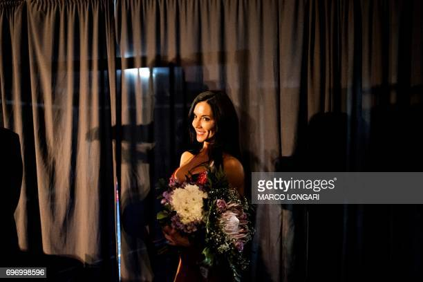 A contestant holds a flower bouquet after winning her category event at the Miss SA Xtreme fitness and bodybuilding show in Pretoria on June 17 2017...
