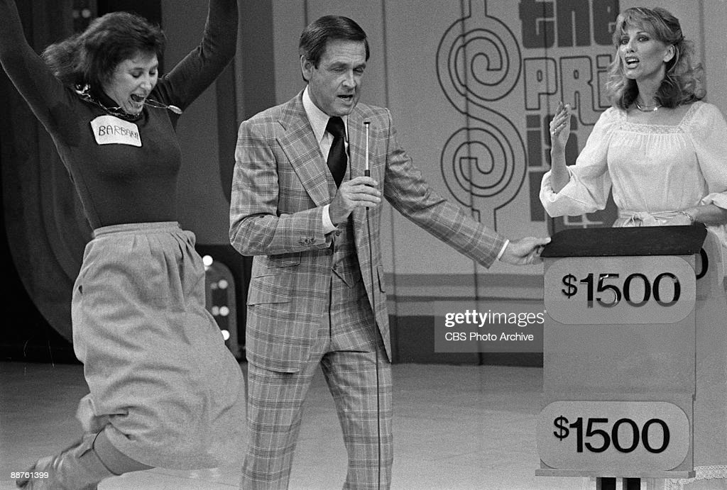 A contestant named Barbara leaps for joy while host Bob Barker and model Janice Pennington share the stage on 'The Price Is Right' February 1978