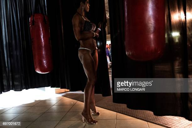 A contestant observes from behind a curtain the Miss SA Xtreme fitness and bodybuilding show in Pretoria on June 17 2017 Dozens of local bodybuilding...