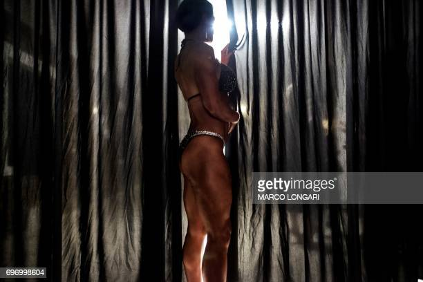 A contestant observes the Miss SA Xtreme fitness and bodybuilding show from behind a curtain in Pretoria on June 17 2017 Dozens of local bodybuilding...