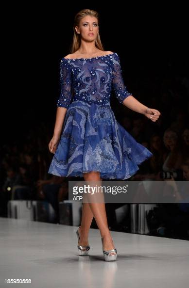 Contestant of the Miss Universe 2013 beauty pageant Miss Great Britain 2013 Amy Willerton displays a creation by Lebanese designer Tony Ward during...