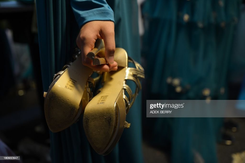 A contestant of the Muslimah World pageant holds a pair of shoes while preparing backstage for the grand final of the contest in Jakarta on September 18, 2013. The finale of a beauty pageant exclusively for Muslim women will take place in the Indonesian capital on September 18, in a riposte to the Miss World contest in Bali that has drawn fierce opposition from Islamic radicals.