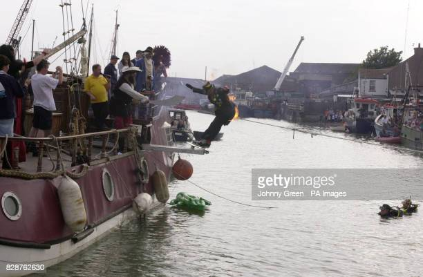 A contestant who has set fire to himself takes part in the 7th World Walking the Plank Championships in Queenborough on the Isle of Sheppey in Kent A...