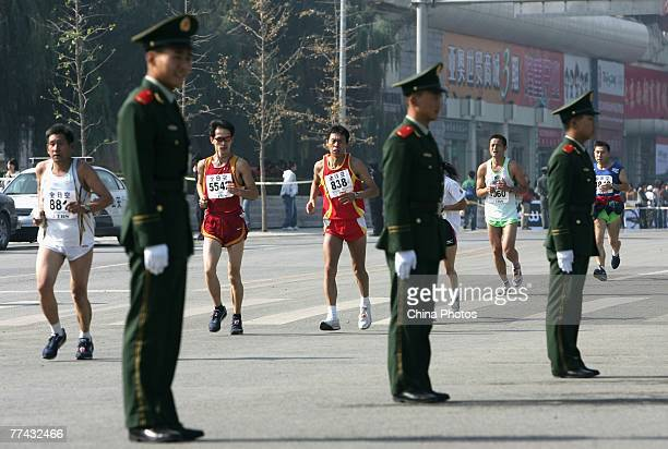 Contestants compete in the race as paramilitary policemen guard during the 2007 Beijing International Marathon on October 21 2007 in Beijing China...