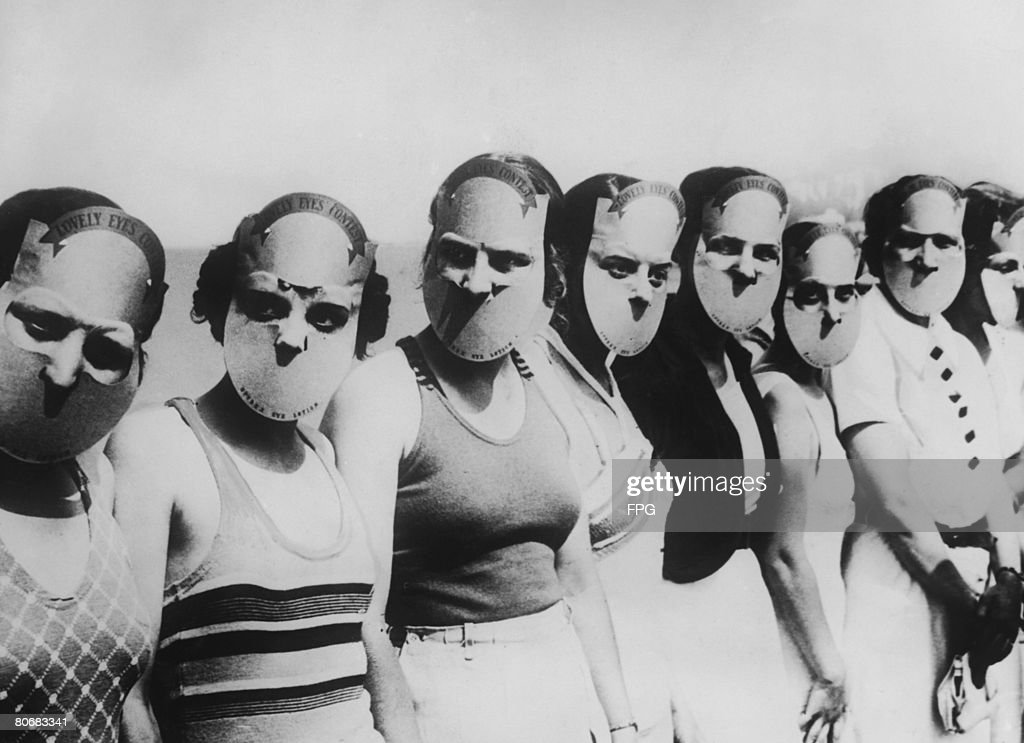 Contestants in the Miss Lovely Eyes beauty pageant in Florida wearing masks to obscure the rest of their faces, circa 1930.