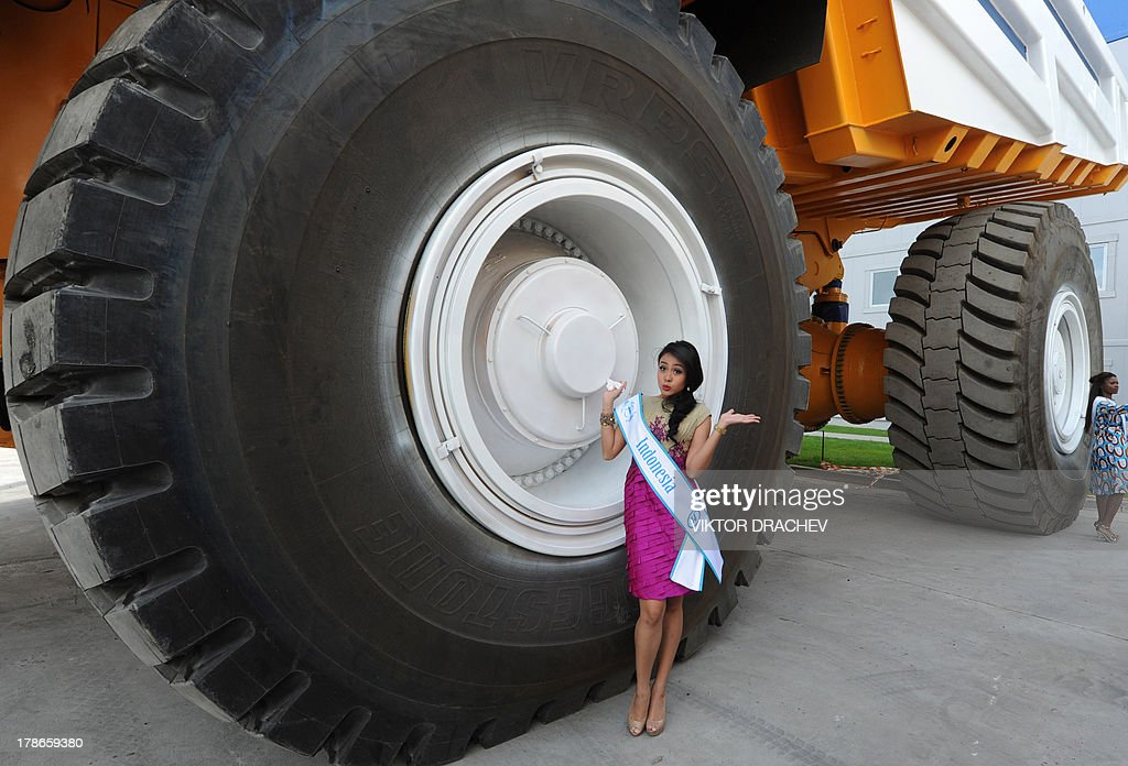 A contestants of Miss Supranational 2013 beauty contest, Cok Krisnanda of Indonesia (L), poses for a photo near a huge 360 ton payload BelAZ mining dump truck during their visit to the BelAZ plant in the Belarus city of Zhodino, some 55 km north of the capital Minsk, on August 30, 2013. On September 6 Belarus capital Minsk hosts Miss Supranational 2013, an annual international beauty contest run by the World Beauty Association based in Panama.