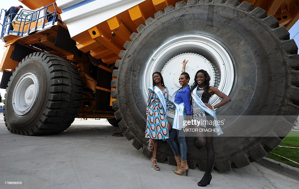 Contestants of Miss Supranational 2013 beauty contest pose for a photo near a huge 360 ton payload BelAZ mining dump truck during their visit to the BelAZ plant in the Belarus city of Zhodino, some 55 km north of the capital Minsk, on August 30, 2013. On September 6 Belarus capital Minsk hosts Miss Supranational 2013, an annual international beauty contest run by the World Beauty Association based in Panama. AFP PHOTO / VIKTOR DRACHEV