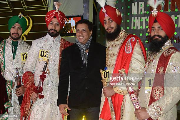Contestants pose with Bollywood film director Madhur Bhandarkar as they display traditional Sikh wedding groom attire during the Mr Singh...