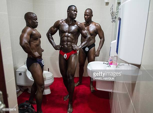 Contestants prepare in the restroom moments before the Most Muscular Man Tanzania competition in Tanzania's capital Dar es Salaam on August 30 2015...