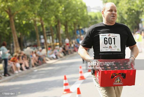 Contestants run with crates of beer during the Waiters' Derby on August 4 2013 in Berlin Germany At the annual event brought back into existence in...