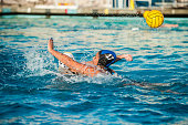 Female water polo player on defense has hand up to block shot as pool water splashes.