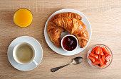 continental Breakfast - coffee, croissant with jam, strawberries and orange juice on wooden background - top view