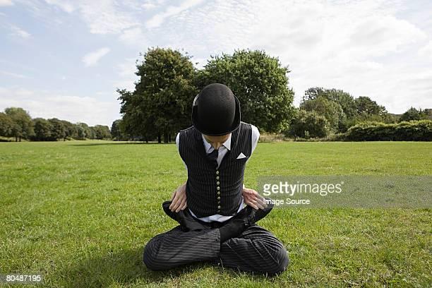 Contorsionniste assis dans un champ
