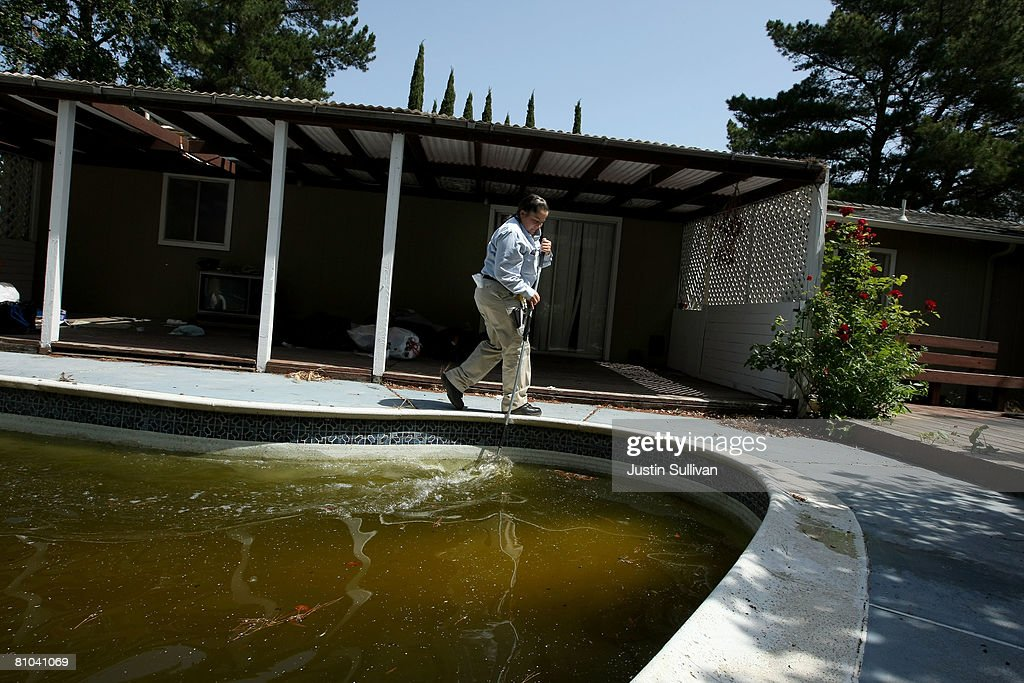 Contra Costa County Mosquito and Vector Control District technician Josefa Cabada turns the water in a neglected pool at a foreclosed home May 9, 2008 in Concord, California. As home foreclossures continue to rise, neglected pools in foreclosed homes are becoming breeding grounds for mosquitos which may carry the West Nile virus. The Contra Costa County Mosquito and Vector District has seen a spike in calls from concerned citizens about abandoned pools and responds by treating the pools with chemicals and the release of fish that eat mosquito larvae.