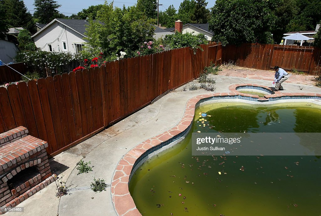 Contra Costa County Mosquito and Vector Control District technician Josefa Cabada inspects a neglected pool at a foreclosed home May 9, 2008 in Concord, California. As home foreclossures continue to rise, neglected pools in foreclosed homes are becoming breeding grounds for mosquitos which may carry the West Nile virus. The Contra Costa County Mosquito and Vector District has seen a spike in calls from concerned citizens about abandoned pools and responds by treating the pools with chemicals and the release of fish that eat mosquito larvae.