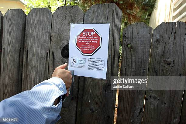 Contra Costa County Mosquito and Vector Control District technician Josefa Cabada posts a sign on a fence after she treated a neglected pool at a...