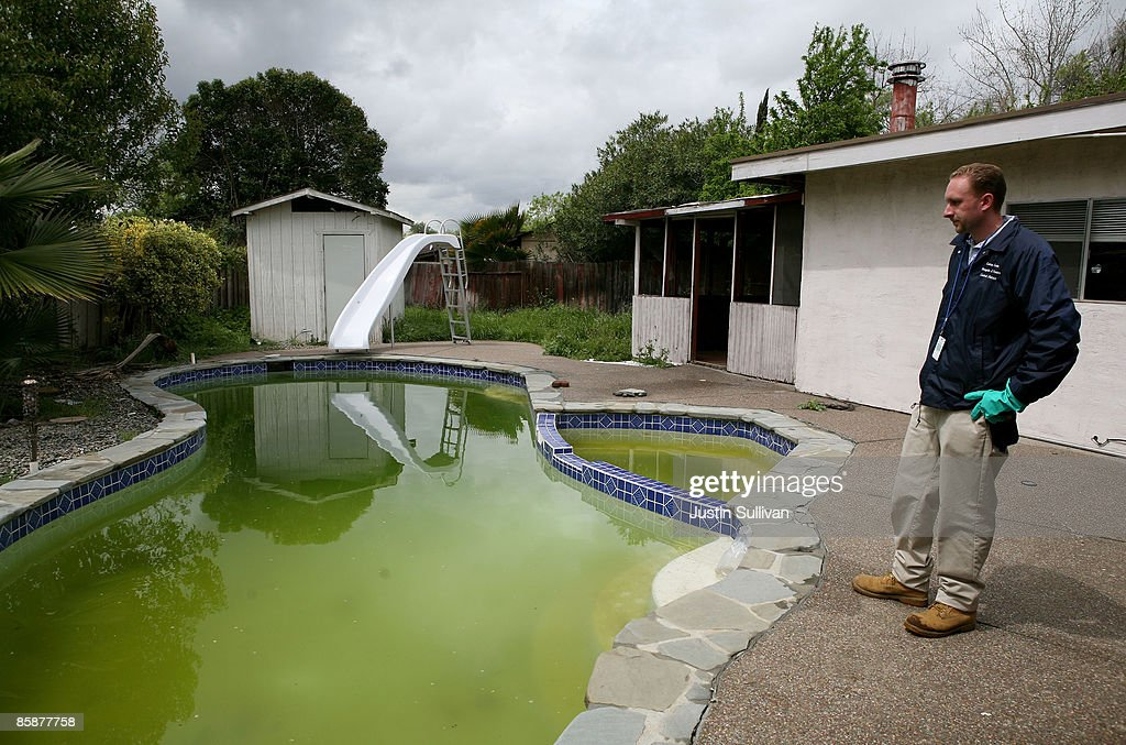 Contra Costa County Mosquito and Vector Control District technician Christopher Doll inspects a neglected pool at a foreclosed home April 9, 2009 in Concord, California. Unseasonably warm weather for Northern California in January appears to have brought female mosquitos out of hibernation and have started to breed months ahead of the normal breeding season. Several groups of mosquitos found in a marsh near the Contra Costa County town of Martinez have tested positive for the West Nile Virus prompting county officials to do more testing and releasing mosquito fish in abandoned pools around the county.