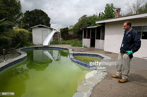 Contra Costa County Mosquito and Vector Control District technician Christopher Doll inspects a neglected pool at a foreclosed home April 9 2009 in...