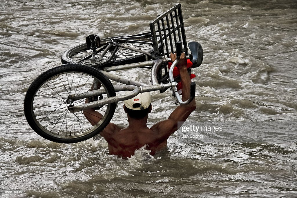 A contraband smuggler carries a bicycle through the river Tachira on the Colombia-Venezuela border, on 3 May 2006 in La Parada, Colombia. Venezuelan gasoline, being 20 times cheaper than in Colombia, is the most wanted smuggling item, followed by food and car parts, while reputable Colombian clothing flow to Venezuela. There are about 25,000 barrels of gasoline crossing illegally the Venezuelan border every day. The risky contraband smuggling, especially during the rainy season when the river rises, makes a living to hundreds of poor families in communities on both sides of the frontier.