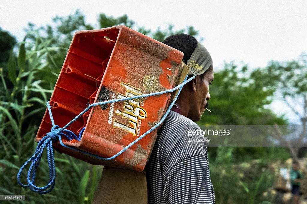A contraband smuggler carries an empty box on the shore of the river Tachira on the Colombia-Venezuela border, on 2 May 2006 in La Parada, Colombia. Venezuelan gasoline, being 20 times cheaper than in Colombia, is the most wanted smuggling item, followed by food and car parts, while reputable Colombian clothing flow to Venezuela. There are about 25,000 barrels of gasoline crossing illegally the Venezuelan border every day. The risky contraband smuggling, especially during the rainy season when the river rises, makes a living to hundreds of poor families in communities on both sides of the frontier.