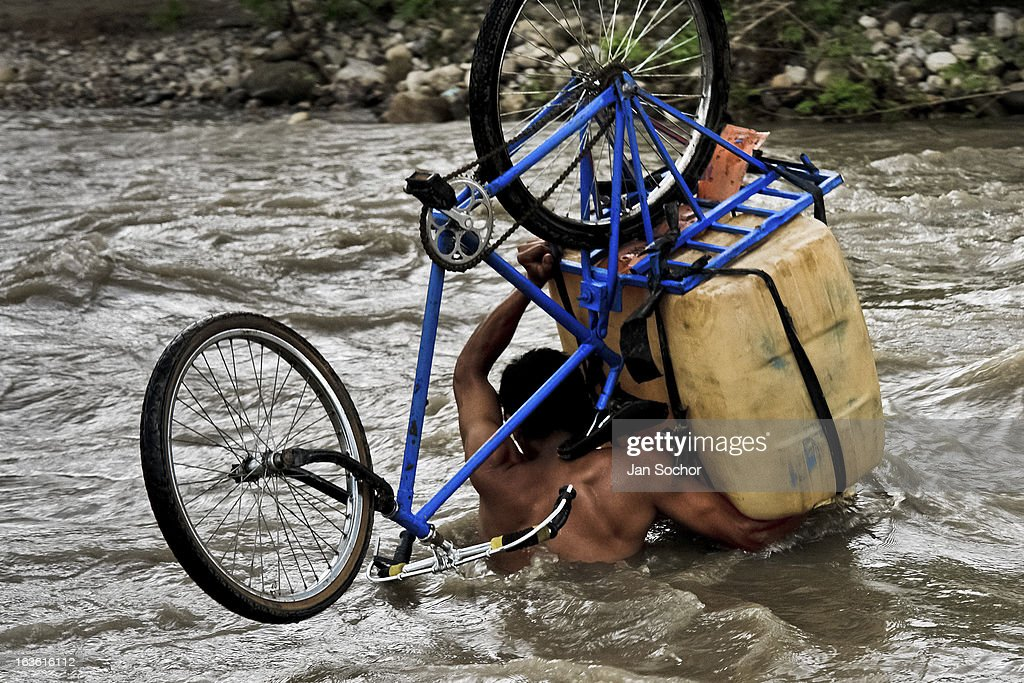 A contraband smuggler carries gasoline barrels on a bicycle through the river Tachira on the Colombia-Venezuela border, on 3 May 2006 in La Parada, Colombia. Venezuelan gasoline, being 20 times cheaper than in Colombia, is the most wanted smuggling item, followed by food and car parts, while reputable Colombian clothing flow to Venezuela. There are about 25,000 barrels of gasoline crossing illegally the Venezuelan border every day. The risky contraband smuggling, especially during the rainy season when the river rises, makes a living to hundreds of poor families in communities on both sides of the frontier.