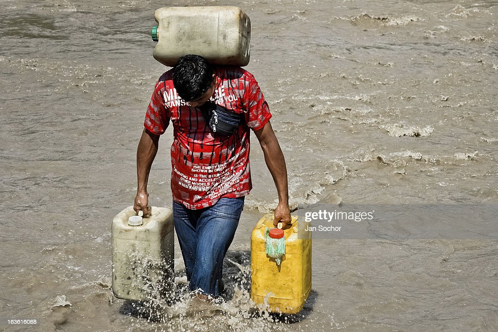 A contraband smuggler carries three barrels of gasoline (90 kg) across the river Tachira on the Colombia-Venezuela border, on 2 May 2006 in La Parada, Colombia. Venezuelan gasoline, being 20 times cheaper than in Colombia, is the most wanted smuggling item, followed by food and car parts, while reputable Colombian clothing flow to Venezuela. There are about 25,000 barrels of gasoline crossing illegally the Venezuelan border every day. The risky contraband smuggling, especially during the rainy season when the river rises, makes a living to hundreds of poor families in communities on both sides of the frontier.