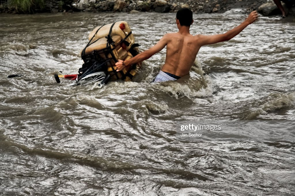 A contraband smuggler, facing wild waves, carries gasoline barrels through the river Tachira on the Colombia-Venezuela border, on 3 May 2006 in La Parada, Colombia. Venezuelan gasoline, being 20 times cheaper than in Colombia, is the most wanted smuggling item, followed by food and car parts, while reputable Colombian clothing flow to Venezuela. There are about 25,000 barrels of gasoline crossing illegally the Venezuelan border every day. The risky contraband smuggling, especially during the rainy season when the river rises, makes a living to hundreds of poor families in communities on both sides of the frontier.