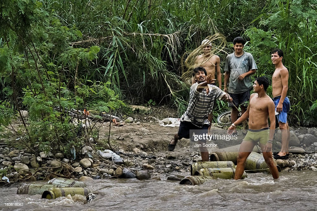 A contraband smuggler throws a rope to his workmate on the shore of the river Tachira on the Colombia-Venezuela border, on 3 May 2006 in La Parada, Colombia. Venezuelan gasoline, being 20 times cheaper than in Colombia, is the most wanted smuggling item, followed by food and car parts, while reputable Colombian clothing flow to Venezuela. There are about 25,000 barrels of gasoline crossing illegally the Venezuelan border every day. The risky contraband smuggling, especially during the rainy season when the river rises, makes a living to hundreds of poor families in communities on both sides of the frontier.