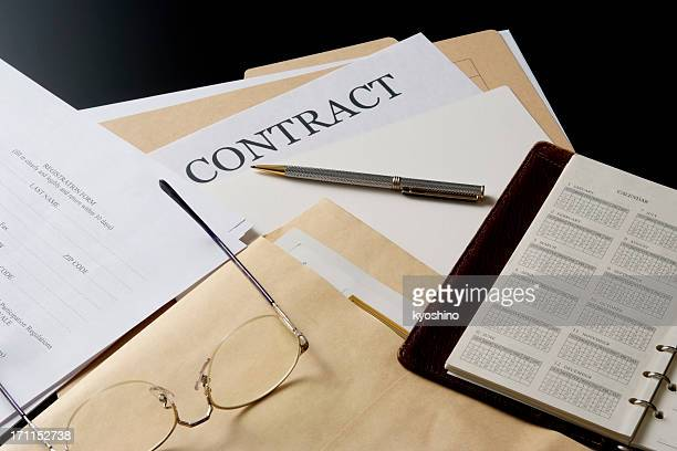 Contract documents and personal organizer on the office desk